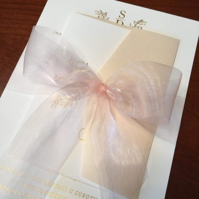 gold foil wedding invitation with blush ribbon bow